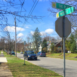 street intersection in neighborhood showing cars and homes